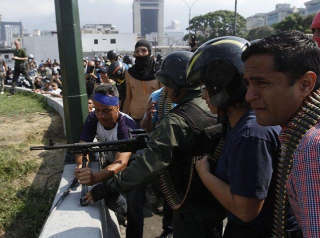 Foto: https://www.laiguana.tv/ En håndfull soldater som støtter opposisjonen forbereder voldelige handlinger i Caracas tirsdag 30. april
